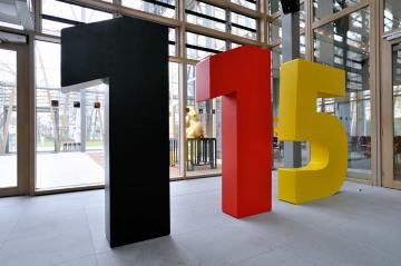 Riesige Zahlen: eine 1 in schwarz, eine 1 in rot und eine 5 in gelb. -